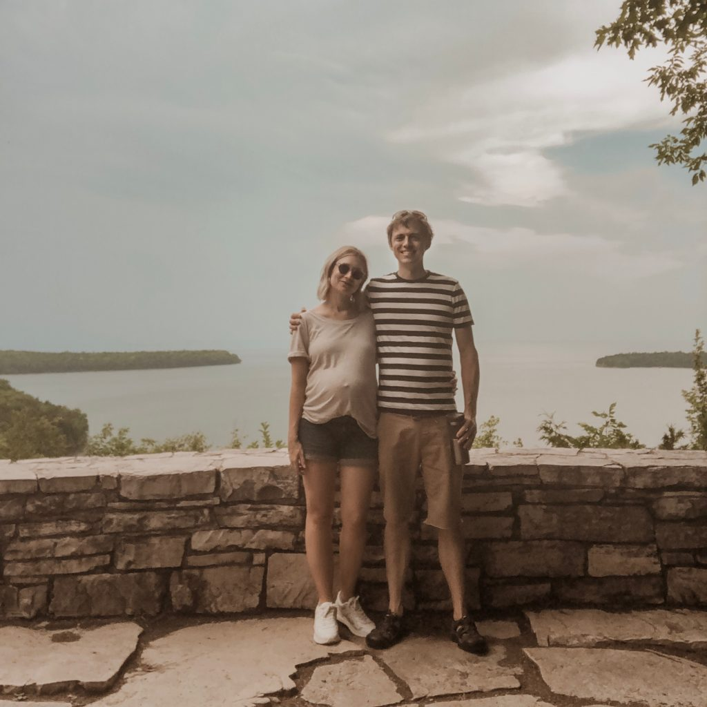 taking a selfie at peninsula state park in door county wisconsin, everlane striped men's tee, men's keen sandals, maternity outfit, maternity shorts, everlane tread sneakers