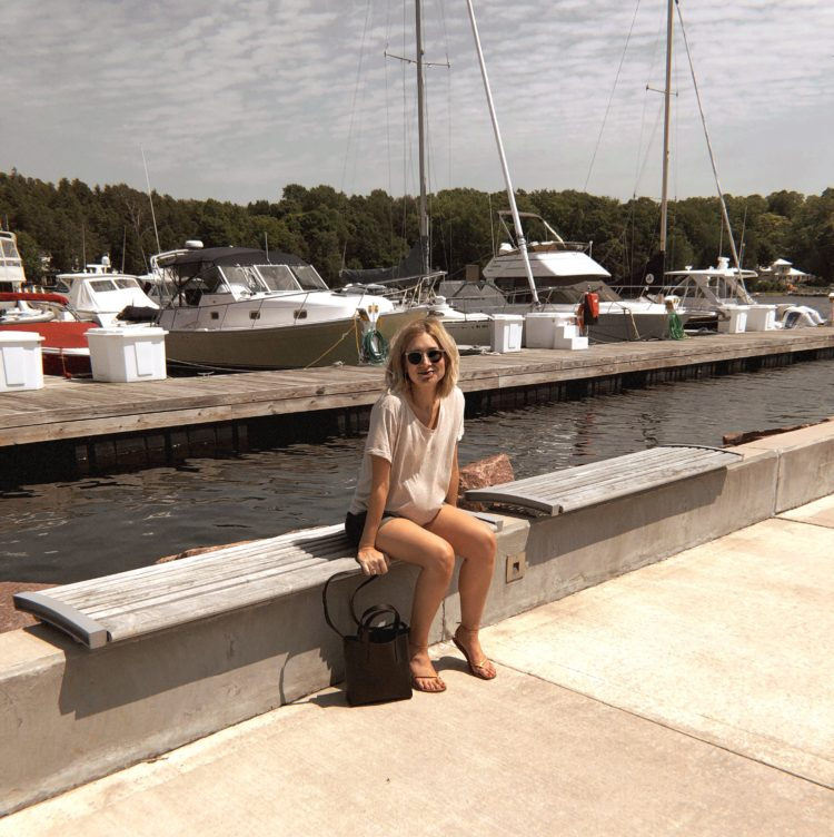 boats in the marina at egg harbor in door county, girl sitting by the dock with sailboats behind her, maternity t-shirt in a neutral color, crocodile bucket bag, blonde shoulder length straight bob